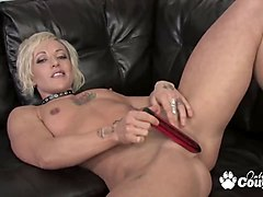 tattooed muscular blond talks to viewer as she does herself on a black leather couch.