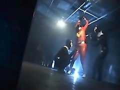 sexy super hero in orange latex is strung up and tortured b